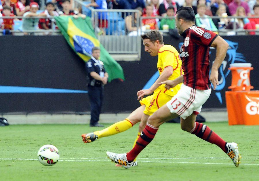 Liverpool's Joe Allen shoots past AC Milan's Adil Rami (13) in the first half during International Champions Cup semifinals at Bank of America Stadium in Charlotte, N.C., on Saturday, Aug. 2, 2014. Liverpool won, 2-0. (David T. Foster, III/Charlotte Observer/MCT)