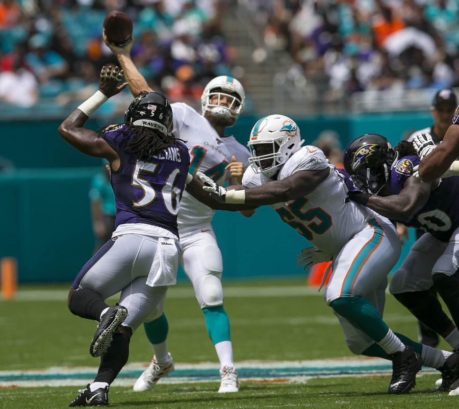 Dolphins quarterback Ryan Fitzpatrick (14) feels the heat against the Ravens. [BILL INGRAM/The Palm Beach Post]