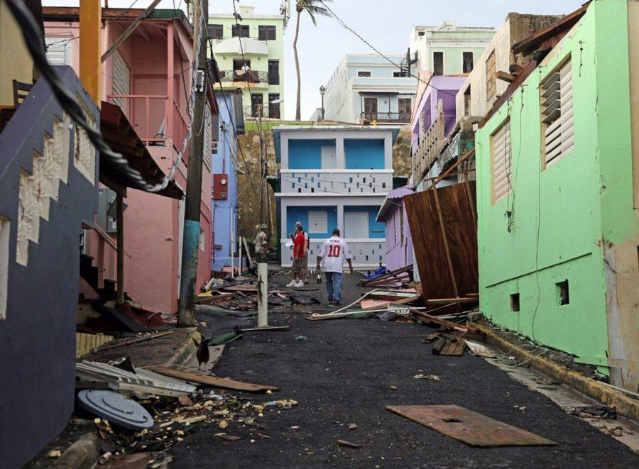 A man walks near colorful damaged buildings.  Residents of San Juan's