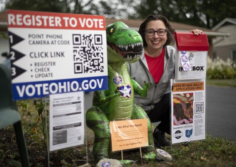 Tiffany Rumbalski sits beside the voting materials, including absentee ballot requests, that she's providing outside her home in Hilliard, Ohio on Tuesday, Sept. 1, 2020. The inflatable tyrannosaurus rex, Vinny Voter, helps draw attention to the display and encourage passers by to take the free materials and get a selfie. (Adam Cairns/The Columbus Dispatch/TNS)
