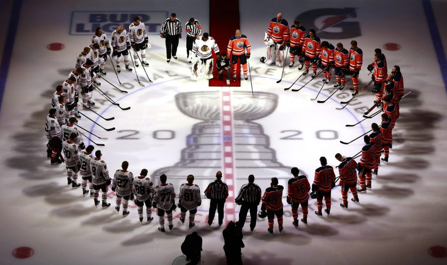The Chicago Blackhawks' Malcolm Subban and the Edmonton Oilers' Darnell Nurse place their hands on Mathew Dumba of the Minnesota Wild during the U.S. national anthem before Game 1 of the Western Conference Qualification Round at Rogers Place in Edmonton, Canada, on Saturday, Aug. 1, 2020. Dumba spoke before the game about the NHL's support of Black Lives Matter and ending racism. (Jeff Vinnick/Getty Images/TNS)