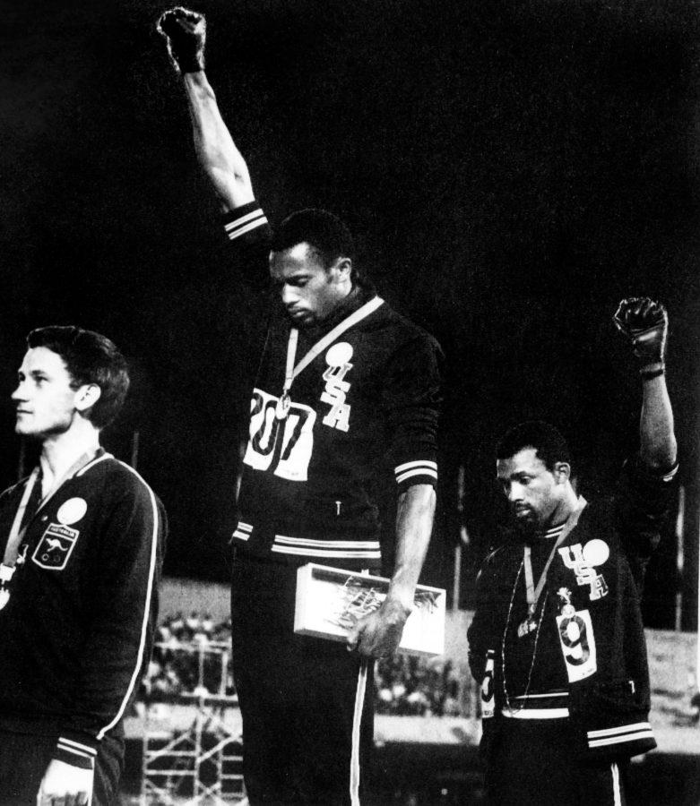 Athletes Tommie Smith, center, and John Carlos, right, raise their gloved fists in the Black Power salute to express their opposition to racism in the United States during the U.S. national anthem, after receiving their medals October 16, 1968, for first and third place in the men's 200m event at the Mexico Olympic Games. At left is Peter Norman of Australia, who took second place. (-/AFP/Getty Images/TNS)