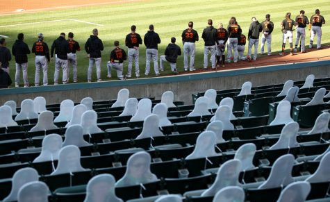 Austin Slater #13 and Jaylin Davis #49 of the San Francisco Giants kneel during the National Anthem before their exhibition game against the Oakland Athletics at Oakland-Alameda County Coliseum on July 20, 2020 in Oakland, California. (Photo by Ezra Shaw/Getty Images/TNS)