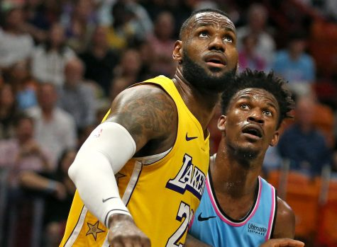 The Los Angeles Lakers' LeBron James, left, jostles for position under the basket with the Miami Heat's Jimmy Butler (22) in the second quarter at the AmericanAirlines Arena in Miami on Friday, Dec. 13, 2019. (David Santiago/Miami Herald/TNS)
