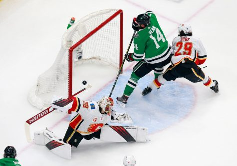The Dallas Stars' Jamie Benn (14) scores a short-handed goal in the first period against Calgary Flames goaltender Cam Talbot (39) in Game 5 of the Western Conference First Round playoff series at Rogers Place in Edmonton, Canada, on Tuesday, Aug. 18, 2020. The Stars won, 2-1, for a 3-2 series lead. (Jeff Vinnick/Getty Images/TNS)