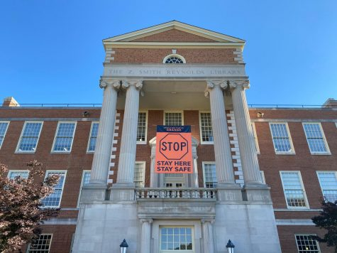 A sign reminding students of the university's Orange operating status hangs between the pillars of the Z. Smith Reynolds Library (Maddie Sayre/Old Gold & Black)
