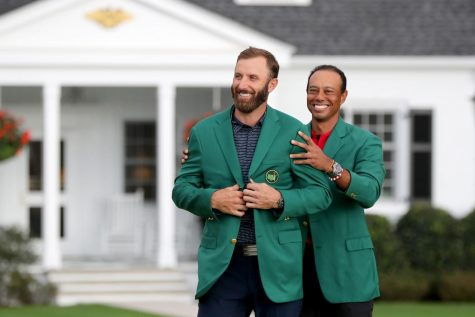 After his breathtaking performance at Augusta National last weekend, Dustin Johnson is presented with the iconic green jacket by last years victor, Tiger Woods (Curtis Compton/Atlanta Journal-Constitution/TNS)