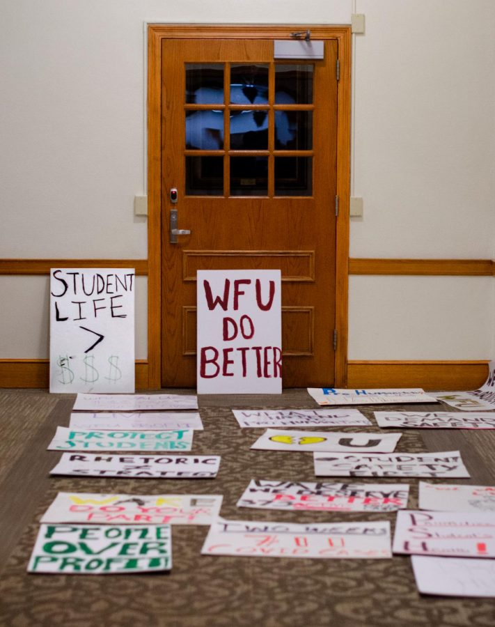 Students leave signs outside of the office of President Nathan O. Hatch to protest perceived poor communication from campus administration on coronavirus-related policies.