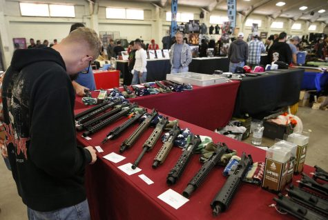 Gun aficionados observe parts of AR-15 semi-automatic rifles at a marketplace in California. The AR-15 has been at the center of the gun-control debate because this weapon has been used to commit atrocities.
