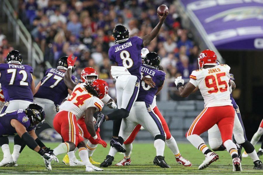 Ravens quarterback Lamar Jackson leaps to find a receiver for a pass.
